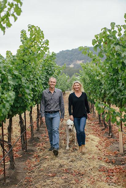 Joel and Sarah Gott walking through their vineyard with their dog